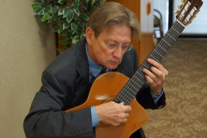 Webmaster Wayne Dooley doubled as entertainer, playing background and Fashion Show music on classical guitar.